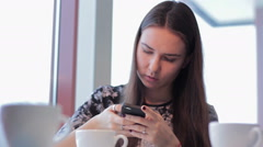 Woman with smartphone drinking cafe latte in cafe Stock Footage