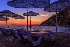 Sunbeds and umbrellas at sunset Stock Photos