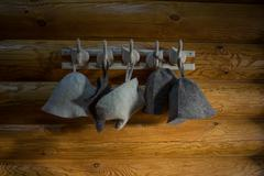 Felt bath hats on hooks wooden wall Stock Photos