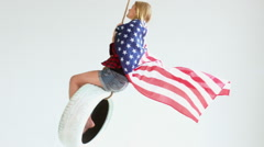Young Caucasian girl with waving American flag riding on a tire swing Stock Footage