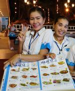 Girls waitresses in seafood restaurant at night - stock photo