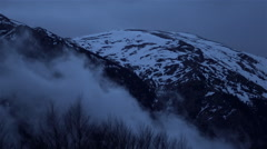 Mists rise at night from snowy mountain Stock Footage