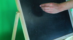 The guy makes a chalk inscription I love you on green background Stock Footage