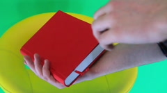 Man looking for something in the book with a green background Stock Footage