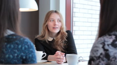 Girl tells the story her girlfriends in cafe Stock Footage