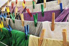 colored clothespins hold the clothes on a rope - stock photo