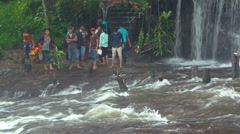 Visitors wading in rushing water at brink of Phnom Kulen Waterfall. video Stock Footage