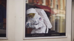 4K Astronaut with cup of coffee, sitting by the window in coffee shop. Stock Footage