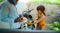 Little girl selling gasoline from glass bottles in Siem Reap. FullHD video Stock Footage