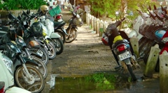 Crowded motorcycle parking area along a sidewalk in Siem Reap. FullHD video Stock Footage