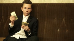 Teenager sitting on the couch counts money Stock Footage