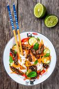 Lamb noodle salad with cucumbers, carrots, chili peppers and mint Stock Photos