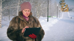 Amazed wow woman looking a tablet application in a snowy mountain on vacations - stock footage