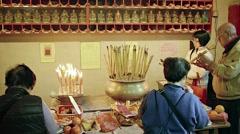Buddhists lighting joss sticks at an altar inside Man Mo Temple. FullHD video Stock Footage