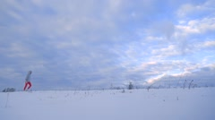 Female in silver jacket and red breeches walking on snow against cloudy sky Stock Footage