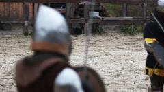 Knight tournament. Two medieval opponents and referee are on the battlefield Stock Footage