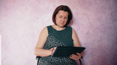 Woman wearing casual and looking business news on digital tablet in the office Stock Footage