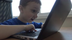 Young child boy works on notebook on the tablet in the room Stock Footage