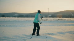 Teenager learning how to ski in the blue sky ant mountains background Stock Footage