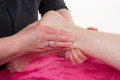 Hands of an osteopath massaging a foot in a room Stock Photos