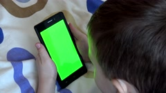 young child boy works on smartphone in bed - green screen  - stock footage