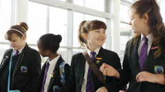4K Young school girls chatting together as they walk through school corridor Stock Footage