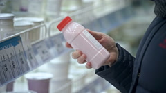 Young woman chooses the yogurt in the supermarket Stock Footage