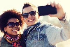 happy teenage friends in shades taking selfie - stock photo
