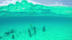 SLOW MOTION: Woman snorkeling underwater exploring statues on sea bottom Stock Footage