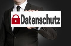 data protection (in german datenschutz) placard is held by businessman - stock photo