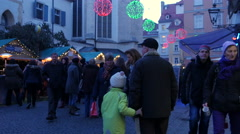 Adults and children walking at the Franziskanerviertel Christmas market in Graz Stock Footage