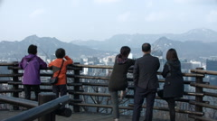 Korean tourists looking down on Seoul from Namsan Mountain Park Stock Footage