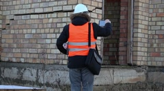 Building inspector filmed at the cracks in the building wall - stock footage