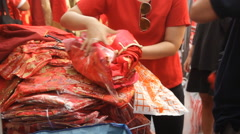Customer buys clothes ahead of the Chinese Lunar New Year celebrations Stock Footage