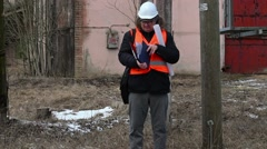 Engineer checking documentation near powerline Stock Footage