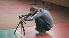 Neanderthal photographer with camera on tripod Stock Footage