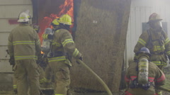 Firefighters struggle with hose - stock footage