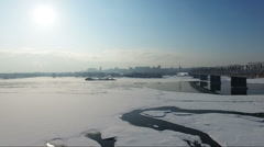 flying over the frozen river in winter. Bridge over river - stock footage