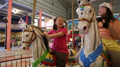 Asian girls mounted carousel in Formosan Aboriginal Culture Village, Taiwan Stock Footage