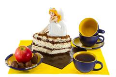 Still Life sweets and tea with a beautiful doll on the cake - stock photo