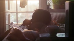 Yound beautiful woman uses a tablet pc on the bed at window wiith sunshine in Stock Footage