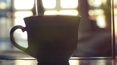 Kettle pouring boiling water into a cup during breakfast in morning sunlight in Stock Footage