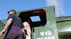 Train driver climbs down from steam train cabin Stock Footage