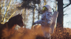 4K Astronaut walking in woodland area looking for signs of life meets wild pony - stock footage
