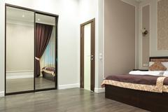 Interior bedroom with mirrored wardrobe Stock Photos