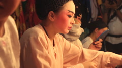 A Chinese opera performer applies make-up before performing Stock Footage