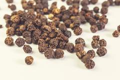 Black pepper isolated on light background. - stock photo