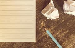 Top view of pencil notepad and crumpled paper on wooden table. Stock Photos