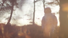 4K Astronaut walking in woodland area looking for signs of life Stock Footage