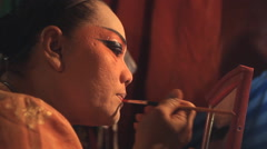 Chinese opera performer applies make-up before performing Stock Footage